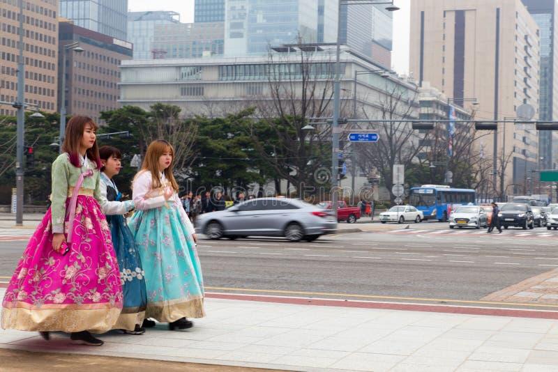 Vrouwelijke toerist drie die buiten Gyeongbokgung-paleis lopen die Koreaanse traditi dragen royalty-vrije stock afbeeldingen
