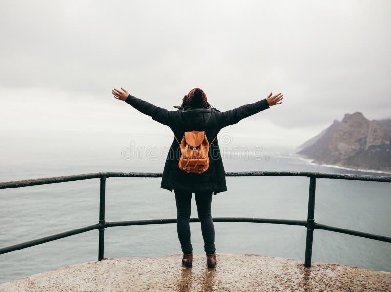Vrouwelijke toerist met haar wapens het uitgestrekte bekijken oceaan royalty-vrije stock afbeeldingen