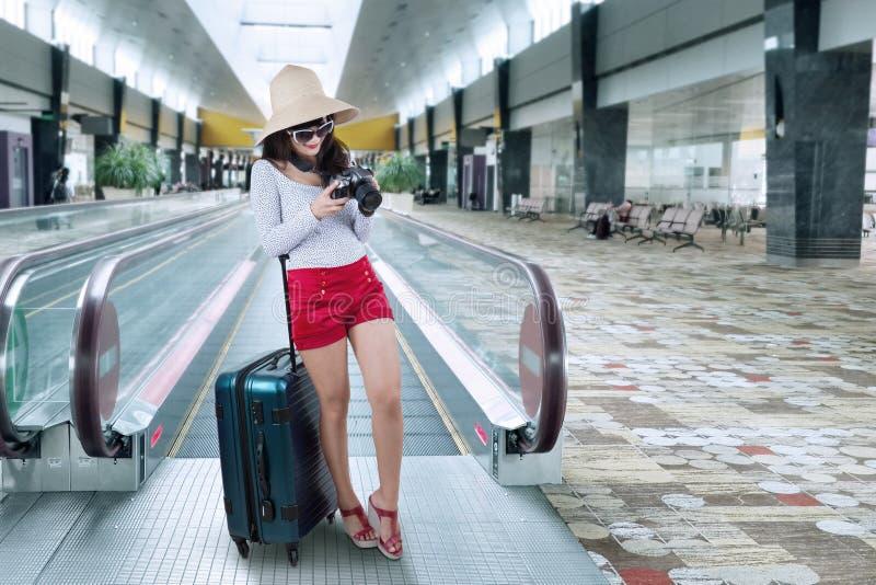 Vrouwelijke toerist op roltrap bij luchthaven stock afbeeldingen