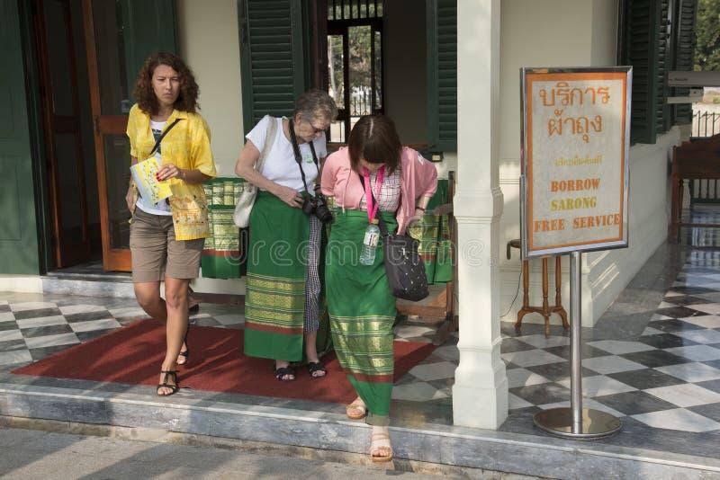 Vrouwelijke toeristen bij borrow een sarongentrefpunt in Thailand stock afbeelding