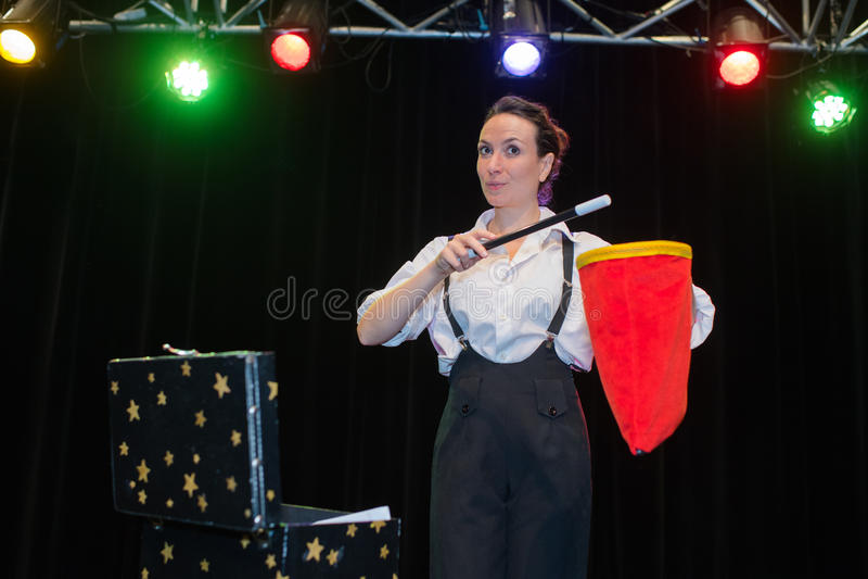 Vrouwelijke tovenaar die truc met toverstokje tonen stock afbeelding