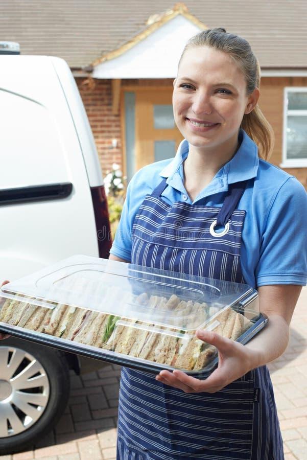 Vrouwelijke Traiteur die Tray Of Sandwiches To House leveren stock afbeeldingen