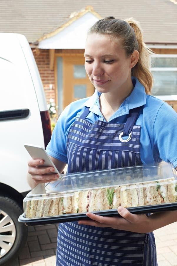 Vrouwelijke Traiteur die Tray Of Sandwiches To House leveren die T controleren stock afbeelding