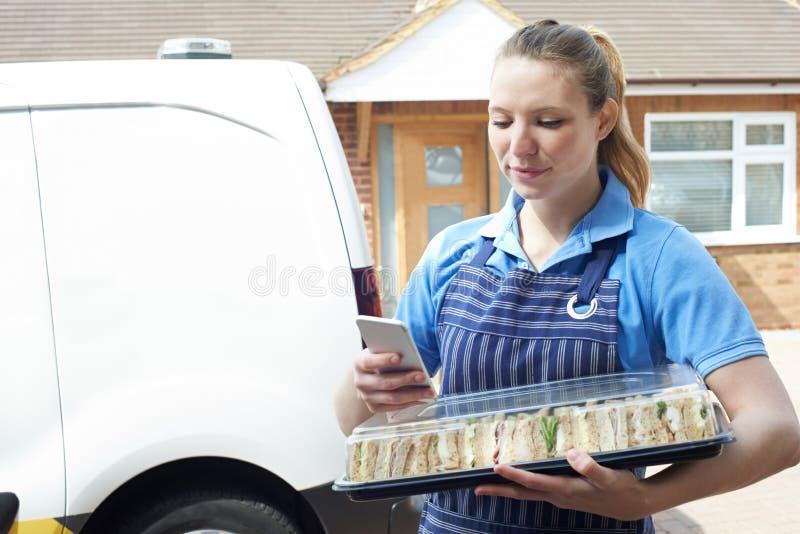 Vrouwelijke Traiteur die Tray Of Sandwiches To House leveren die T controleren royalty-vrije stock foto's
