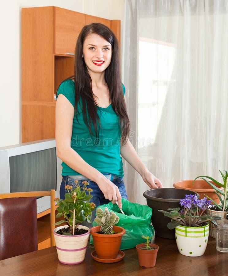 Vrouwelijke tuinman met bloeiende installaties stock afbeelding