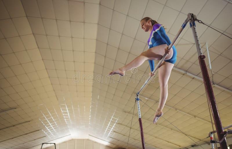 Vrouwelijke turner het praktizeren gymnastiek op de rekstok stock afbeelding