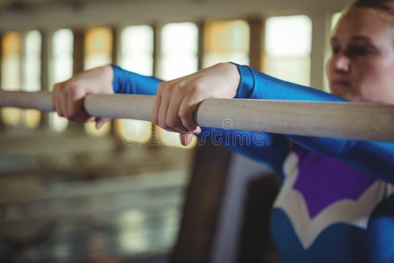 Vrouwelijke turner het praktizeren gymnastiek op de rekstok in het gymnasium stock foto's