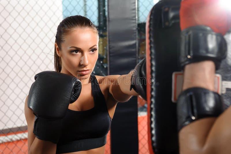 Vrouwelijke vechterstreinen in een het vechten kooi royalty-vrije stock foto