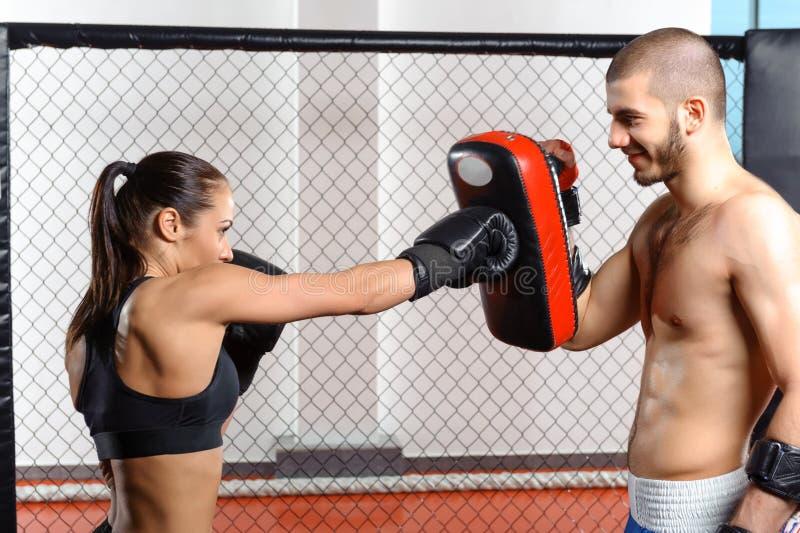 Vrouwelijke vechterstreinen in een het vechten kooi stock afbeelding