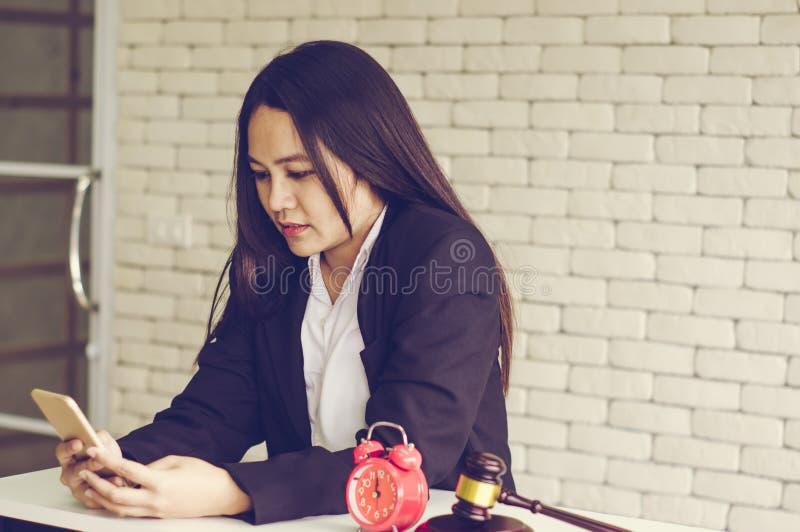 Vrouwelijke veilingmeestercontroles, online de veilingswinnaars van de controlelijst, met retro wekker en gouden bruine houten di royalty-vrije stock foto's