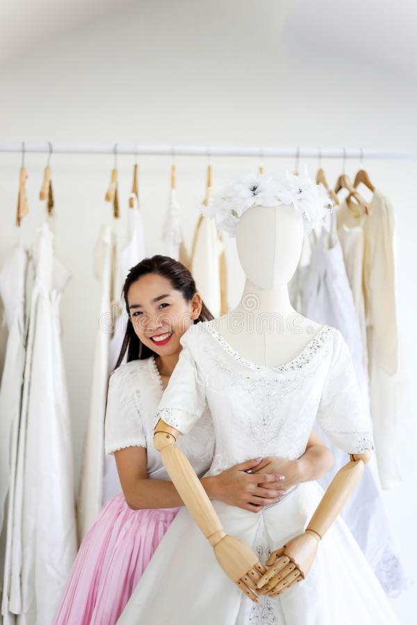 Vrouwelijke verkoopmedewerker in de bridalwear kleding van het opslaghuwelijk in sh stock foto