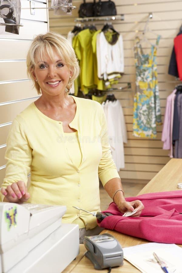 Vrouwelijke verkoopmedewerker in kledingsopslag stock foto's