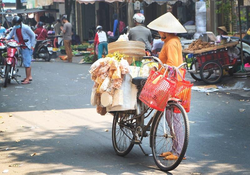 Vrouwelijke verkoper op fiets in een markt van Ho Chi Minh-stad, Vietnam royalty-vrije stock afbeeldingen