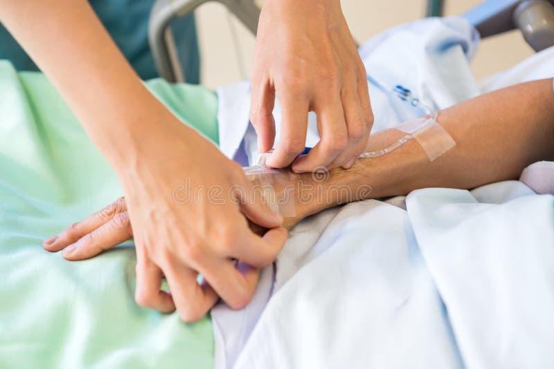 Vrouwelijke Verpleegster Attaching IV Druppel op Mannelijke Patiënt stock foto's