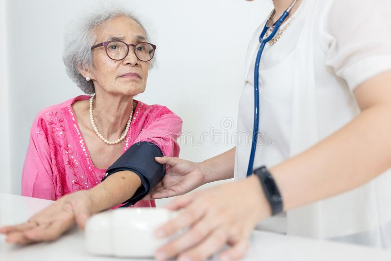 Vrouwelijke verpleegster die bloeddruk van een hogere vrouw controleren thuis, H royalty-vrije stock foto