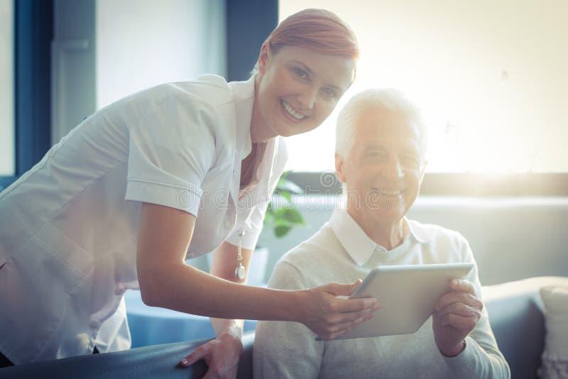 Vrouwelijke verpleegster die medisch rapport aan de hogere mens over digitale tablet tonen royalty-vrije stock fotografie