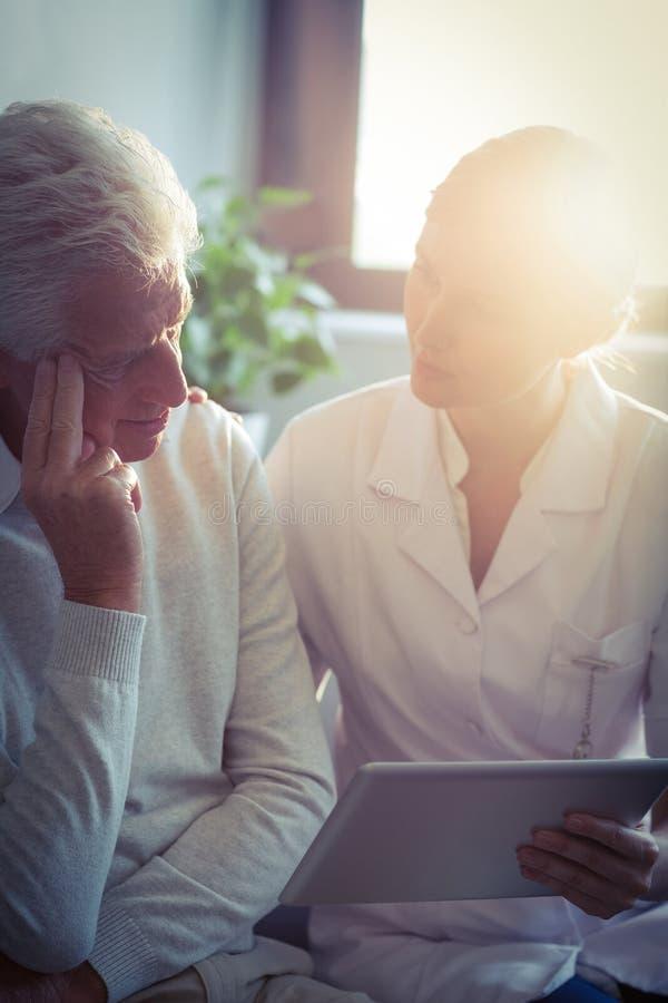 Vrouwelijke verpleegster die medisch rapport aan de hogere mens over digitale tablet tonen stock foto's