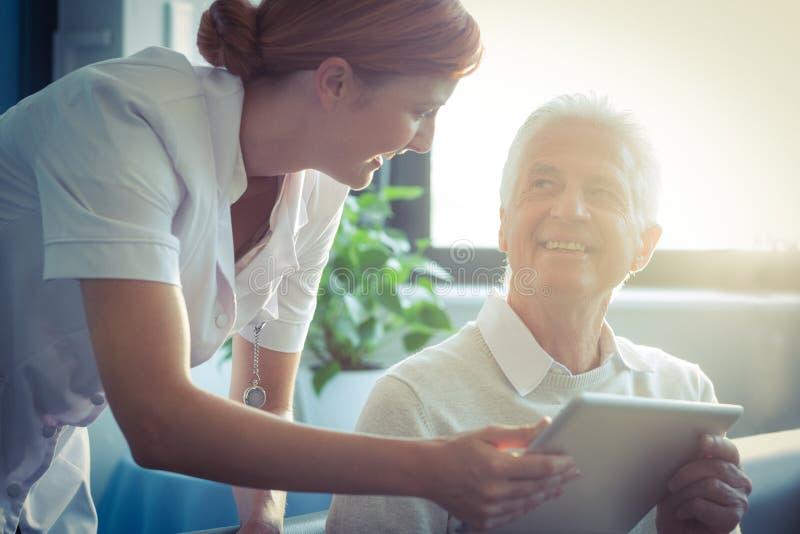 Vrouwelijke verpleegster die medisch rapport aan de hogere mens over digitale tablet tonen stock foto