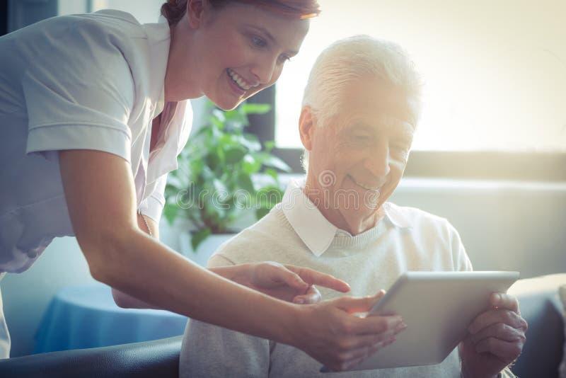 Vrouwelijke verpleegster die medisch rapport aan de hogere mens over digitale tablet tonen stock fotografie