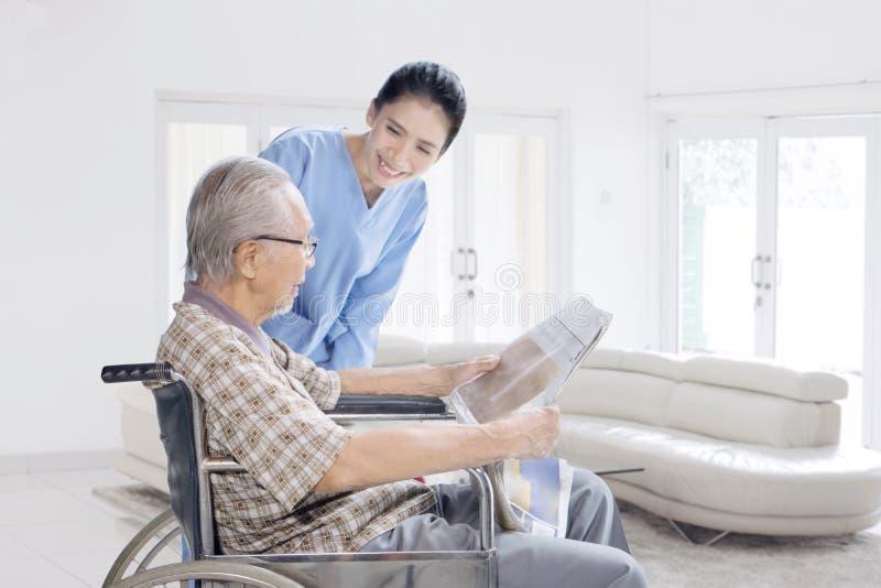 Vrouwelijke verpleegster die met de oude mens thuis spreken stock afbeeldingen