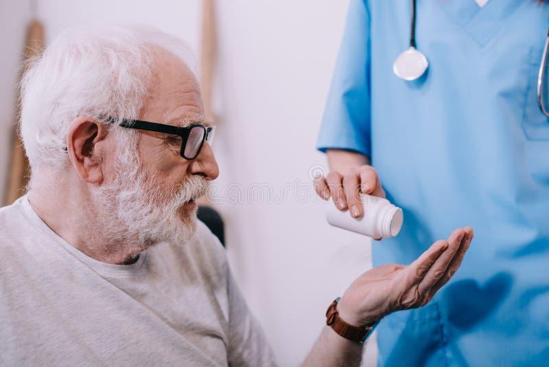 Vrouwelijke verpleegster die pillen geven aan stock fotografie