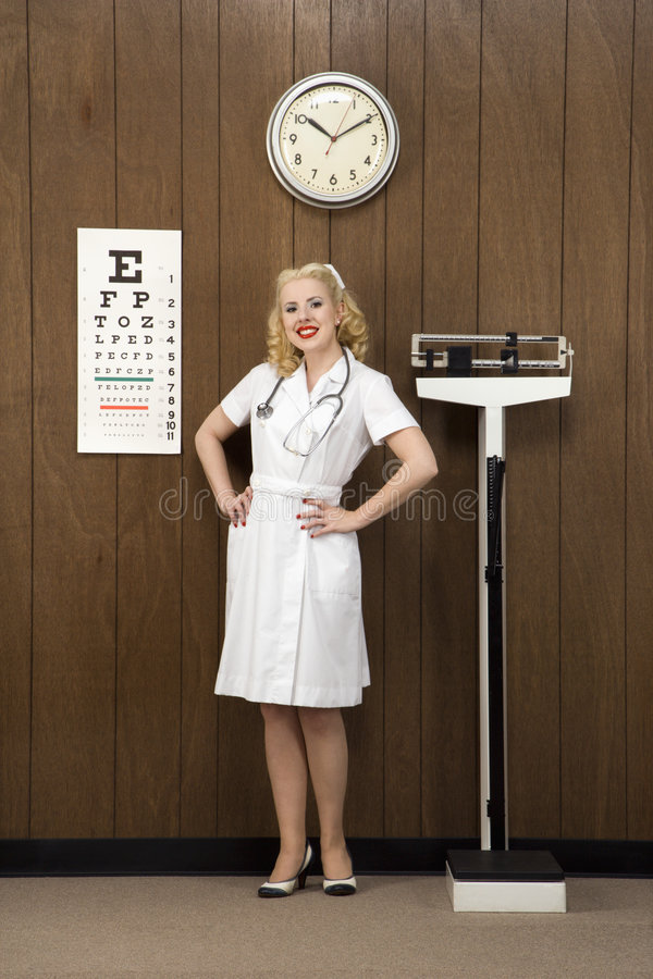 Vrouwelijke verpleegster die zich in het retro plaatsen bevindt. royalty-vrije stock afbeelding