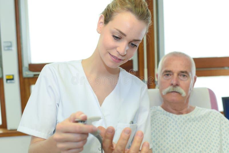 Vrouwelijke verpleegster die zorg oude patiënt nemen royalty-vrije stock foto's