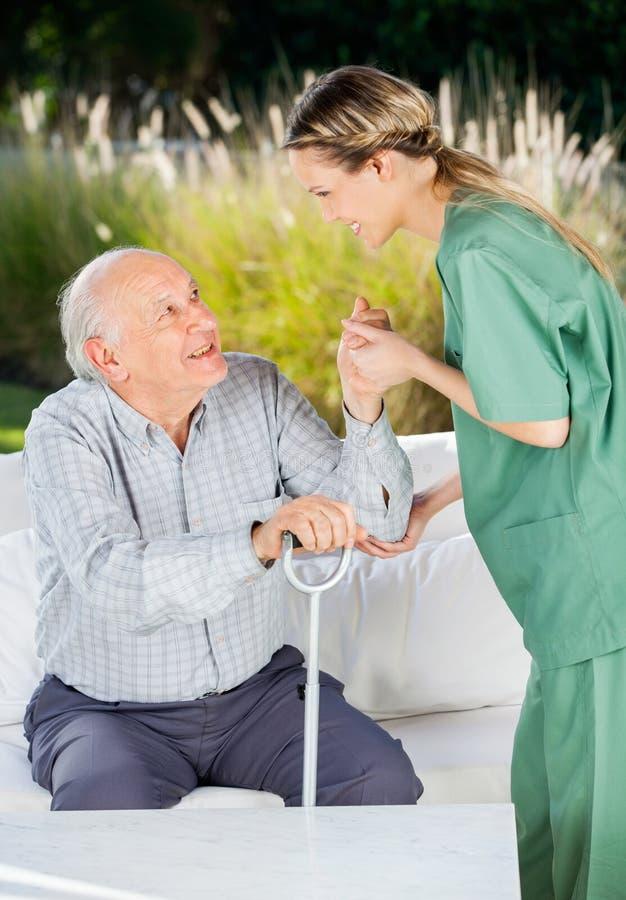 Vrouwelijke Verpleegster Helping Senior Man omhoog Te worden van stock afbeelding