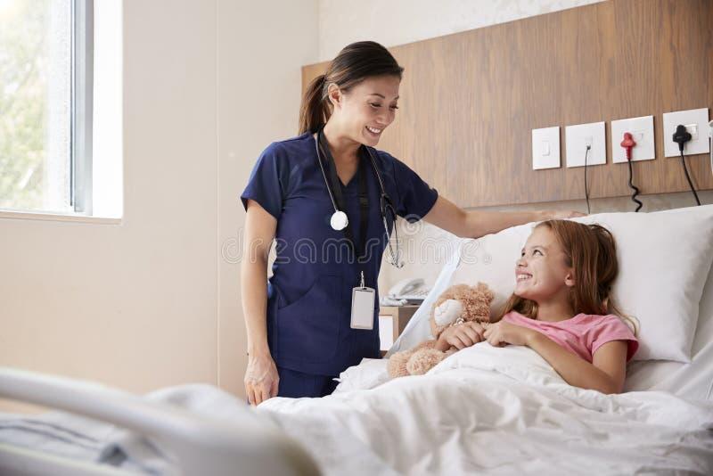 Vrouwelijke Verpleegster Visiting Girl Lying die in het Ziekenhuisbed Teddy Bear koesteren royalty-vrije stock afbeeldingen