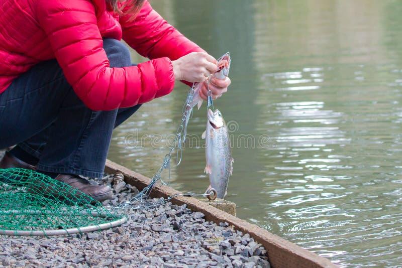 Vrouwelijke visser met een regenboogforel stock afbeeldingen