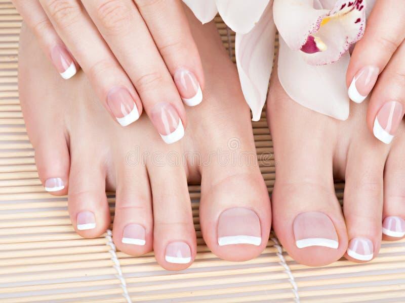 Vrouwelijke voeten bij kuuroordsalon op pedicure en manicureprocedure royalty-vrije stock foto's