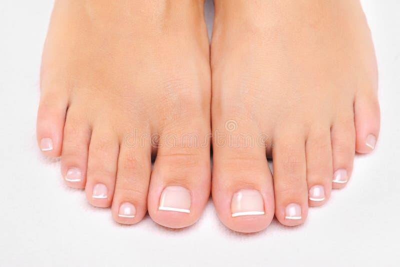 Vrouwelijke voeten met de Franse pedicure royalty-vrije stock afbeelding