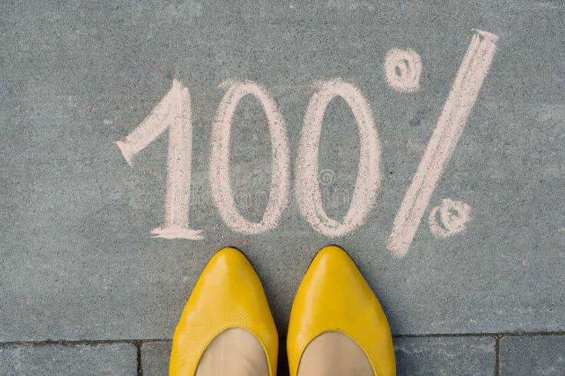 Vrouwelijke voeten met tekst 100 die percenten op grijze stoep worden geschreven stock fotografie