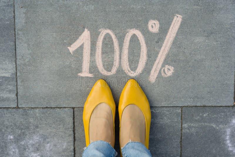 Vrouwelijke voeten met tekst 100 die percenten op grijze stoep worden geschreven royalty-vrije stock afbeelding