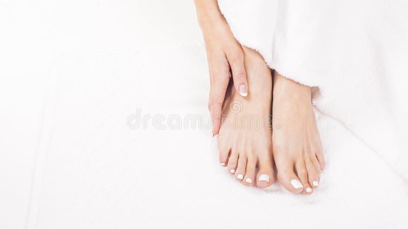 Vrouwelijke voeten op handdoek De spijkers die vers krijgen en nauwkeurig kijken tijdens een pedicureprocedure stock foto