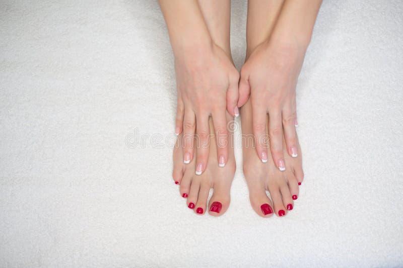 Vrouwelijke voeten op witte badstofhanddoek en handen De vrouw raakt haar huid, omhoog sluit Franse manicure en rode pedicure royalty-vrije stock foto's