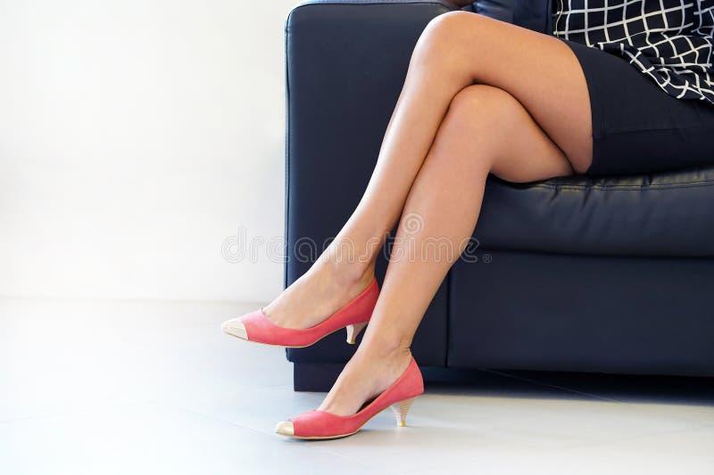 Vrouwelijke voeten in rode schoenen Misdadige prostitutie stock afbeelding