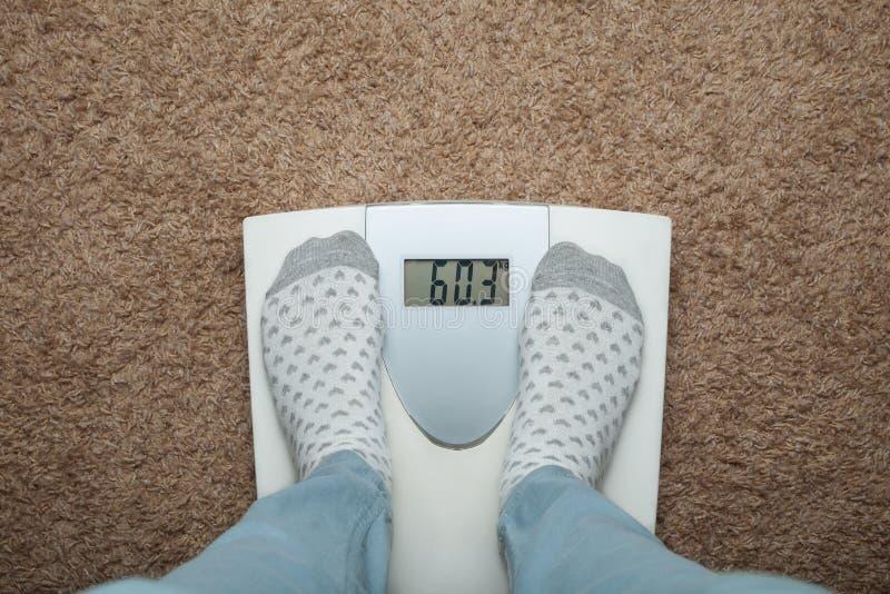 Vrouwelijke voeten in sokken op elektronische schalen Bovenmatig gewicht en dieet royalty-vrije stock afbeelding