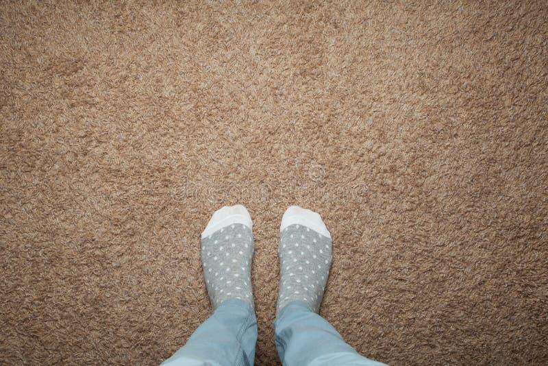 Vrouwelijke voeten in warme sokken tegen een achtergrond van bruin tapijt, ruimte voor tekst stock foto