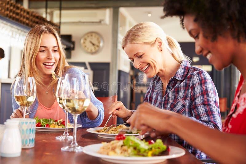 Vrouwelijke vrienden die bij een restaurant eten royalty-vrije stock foto's