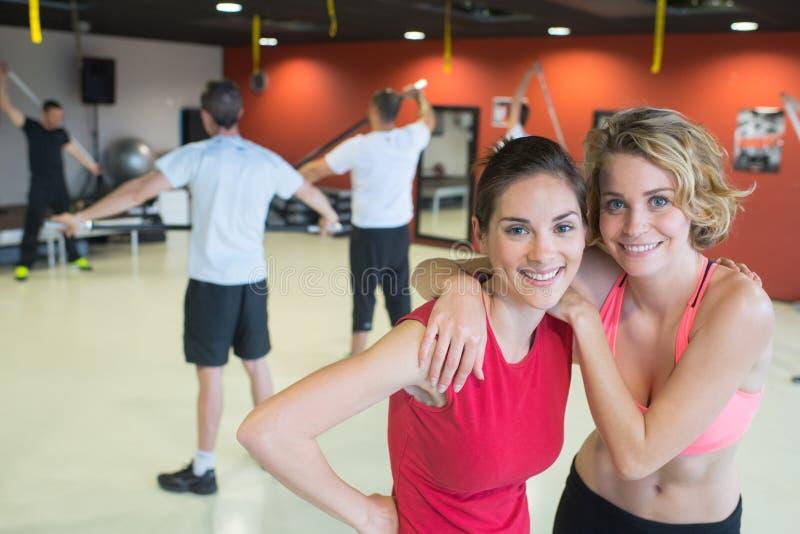 Vrouwelijke vrienden die bij gymnastiek uitoefenen die vreugdevol glimlachen stock afbeeldingen