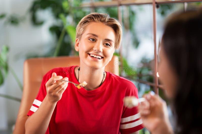 Vrouwelijke vrienden die bij restaurant eten stock foto