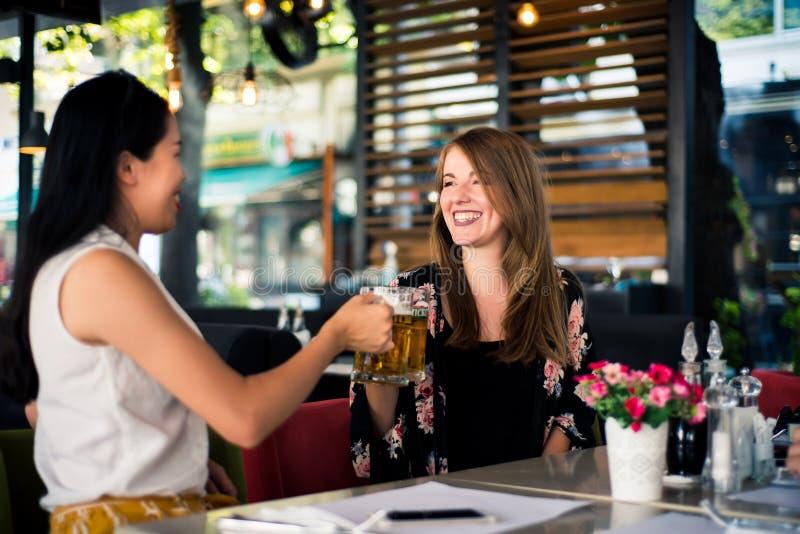 Vrouwelijke vrienden die een bier in een bar hebben royalty-vrije stock foto