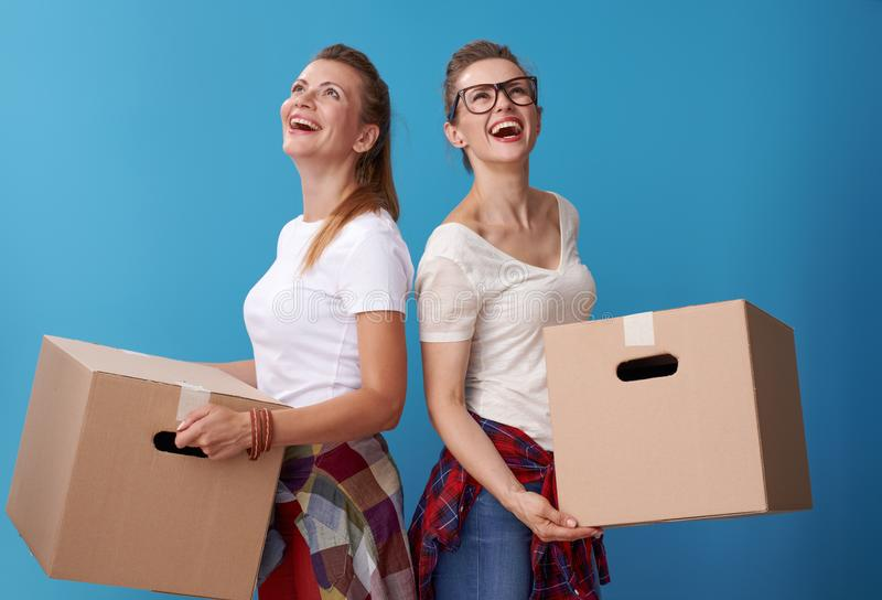 Vrouwelijke vrienden die een kartonvakjes houden en omhoog exemplaar bekijken royalty-vrije stock foto's