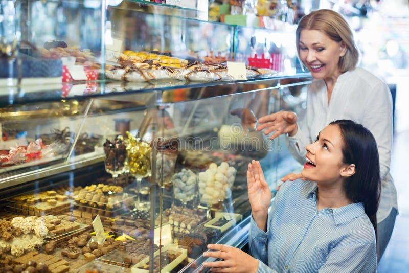 Vrouwelijke vrienden die fijne chocolade en banketbakkerij selecteren bij ca royalty-vrije stock foto