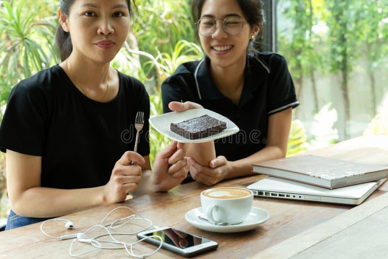 Vrouwelijke vrienden die koffiepauze met browniecake hebben in koffiewinkel royalty-vrije stock afbeeldingen