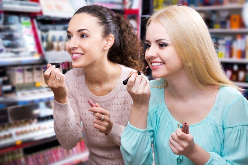 Vrouwelijke vrienden die lipgloss selecteren royalty-vrije stock afbeelding