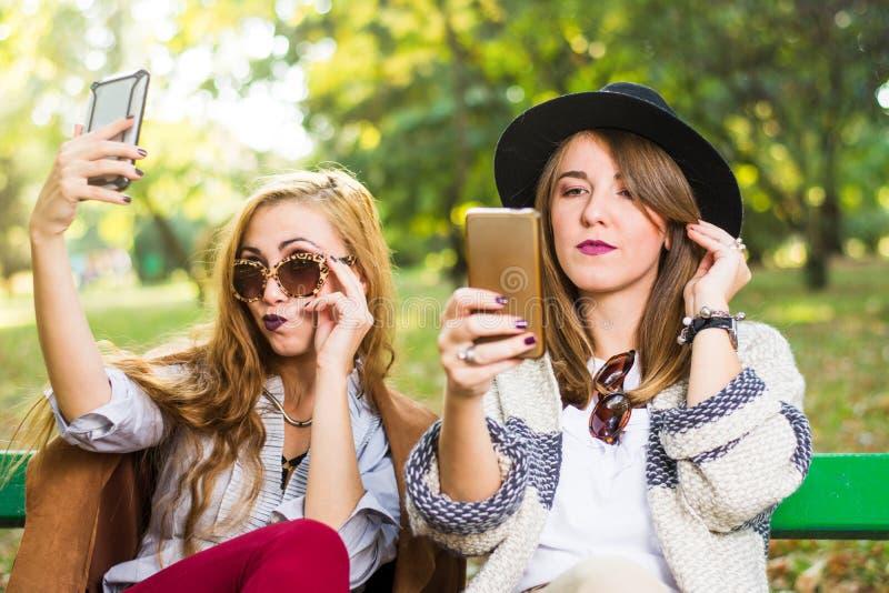 Vrouwelijke vrienden die met telefoon in het park roddelen royalty-vrije stock afbeeldingen