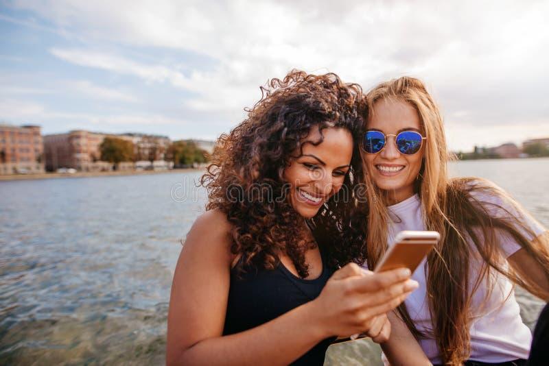 Vrouwelijke vrienden die slimme telefoon met behulp van door het meer stock afbeeldingen