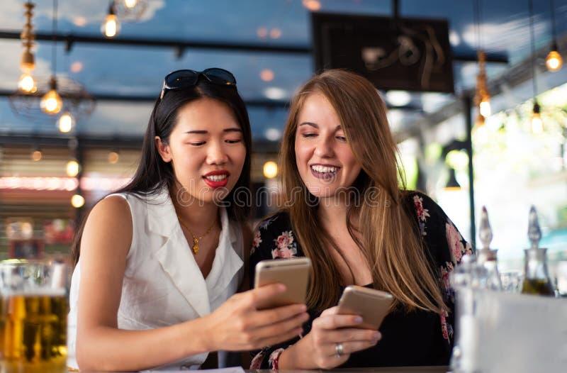Vrouwelijke vrienden die telefoon in het restaurant met behulp van royalty-vrije stock foto
